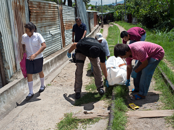 A girl looks away from the body of an assassinated man, who was killed by a gang member in San Salvador.
